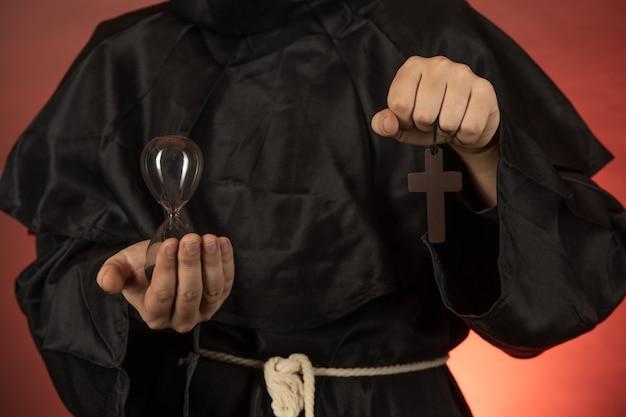 Um homem com uma batina monástica segura uma ampulheta e um crucifixo nas mãos