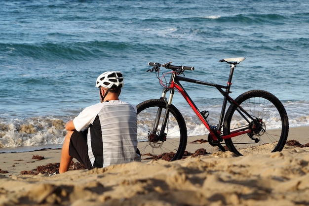Um homem com uma bicicleta está descansando na praia do oceano atlântico. senta-se na areia. vista traseira.