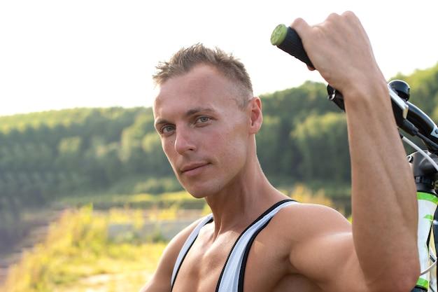 Um homem com uma bicicleta na natureza. no campo, no verão. para qualquer propósito.