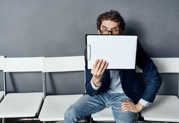 Um homem com uma caixa se senta em uma cadeira com coisas documentos dispensa