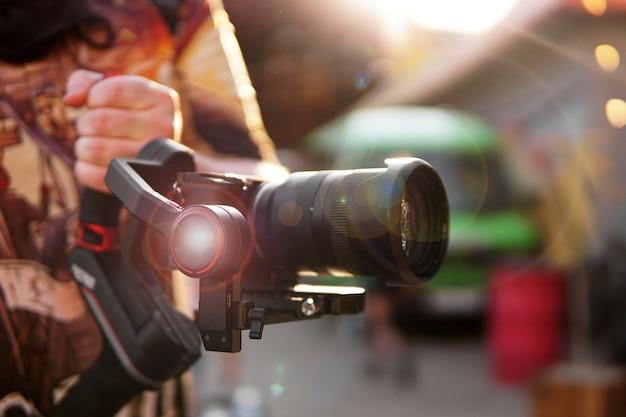Um homem com uma câmera e uma fotocâmera de lente para filmagem