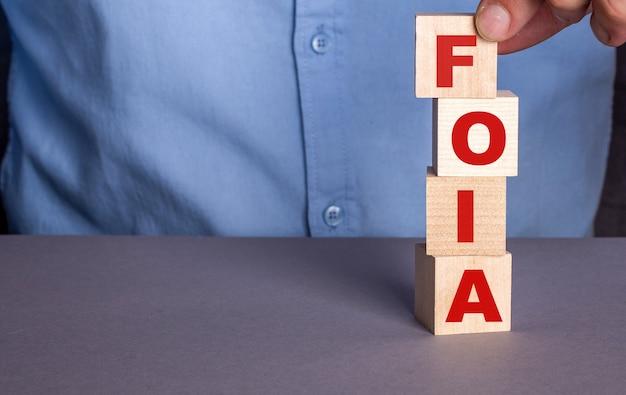 Um homem com uma camisa azul compõe a palavra foia the freedom of information act a partir de cubos de madeira verticalmente