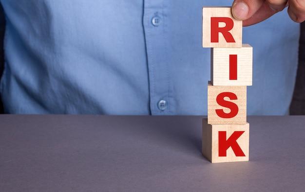 Um homem com uma camisa azul compõe a palavra risco com cubos de madeira verticalmente