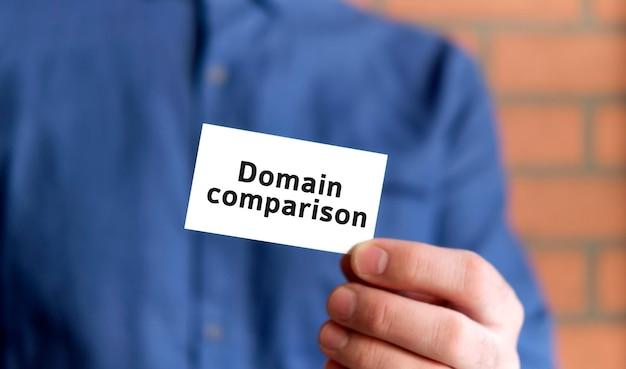 Um homem com uma camisa azul segura uma placa com o texto da comparação de domínio em uma das mãos