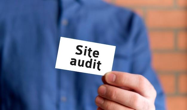 Um homem com uma camisa azul segura uma placa com o texto de auditoria do site em uma das mãos