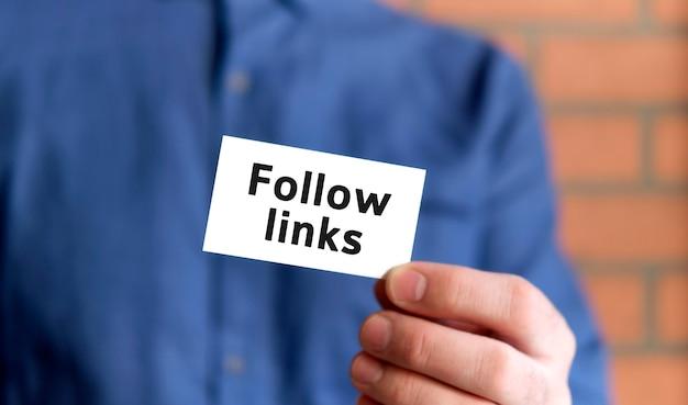 Um homem com uma camisa azul segura uma placa com o texto dos links para seguir em uma das mãos