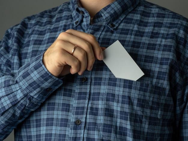 Um homem com uma camisa azul xadrez enfia um cartão de visita no bolso da camisa.