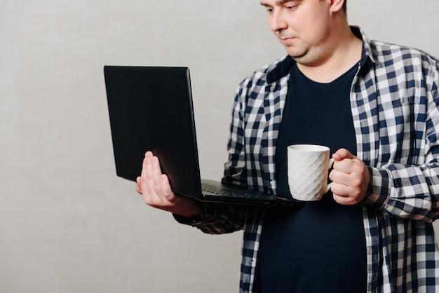 Um homem com uma camisa com um laptop e uma xícara de café na mão contra uma parede cinza