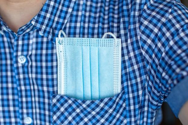 Um homem com uma camisa e no bolso uma máscara médica de covid-19. o conceito de turismo e viagens no novo normal após o covid-19, o coronavírus. a vida na cidade e a sociedade durante a pandemia