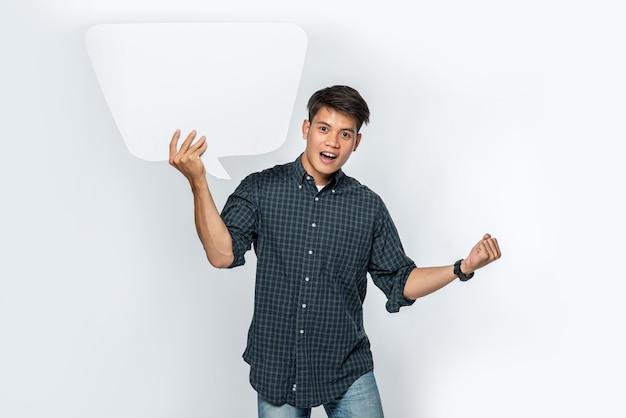 Um homem com uma camisa escura segura um símbolo de caixa de pensamento