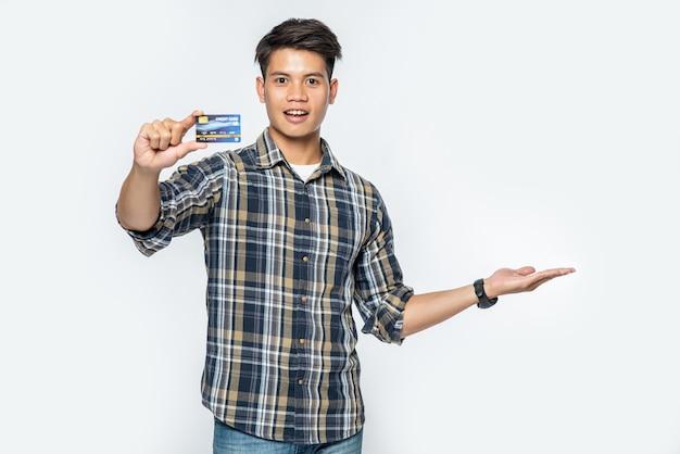 Um homem com uma camisa listrada abre a mão esquerda e segura um cartão de crédito