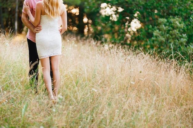 Um homem com uma camisa rosa e uma mulher com um vestido branco curto estão abraçados entre as espigas atrás