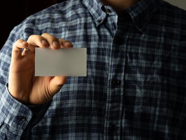 Um homem com uma camisa xadrez coloca um cartão de visita no bolso da camisa. copie o espaço