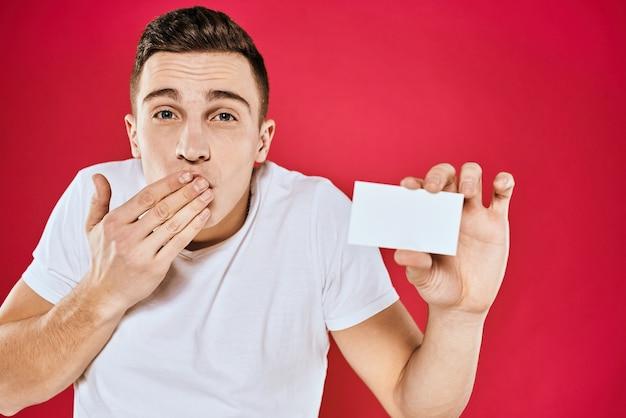 Um homem com uma camiseta branca com um cartão de visita nas mãos emoções
