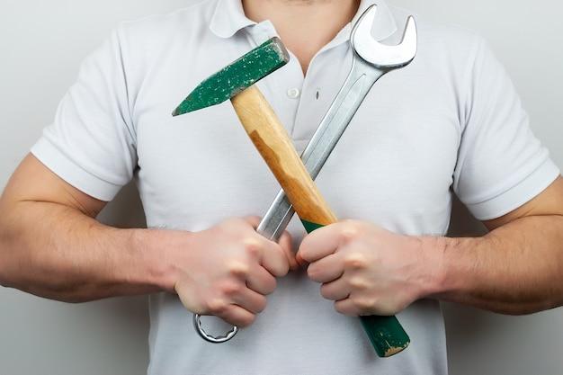 Um homem com uma camiseta branca com um martelo e uma chave inglesa, segurando-os em cruz