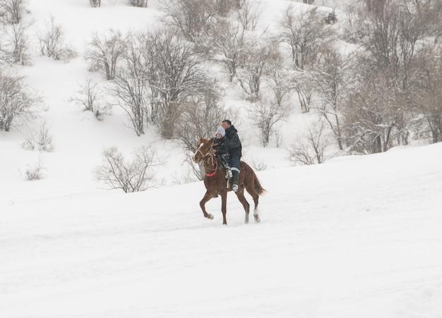 Um homem com uma criança em um cavalo nas montanhas de inverno