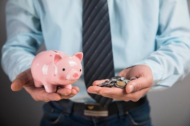 Um homem com uma das mãos segura um cofrinho nas outras moedas