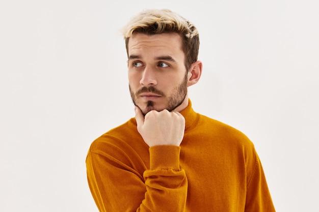 Um homem com uma expressão séria olhar para o close-up do estilo de vida de roupas da moda ao lado. foto de alta qualidade