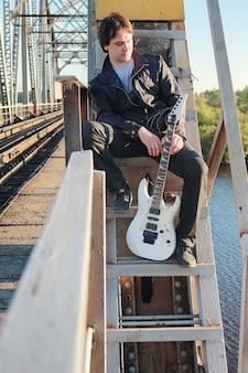Um homem com uma guitarra elétrica na paisagem industrial ao ar livre