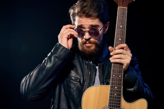Um homem com uma guitarra nas mãos jaqueta de couro música performance rock star estilo moderno escuro