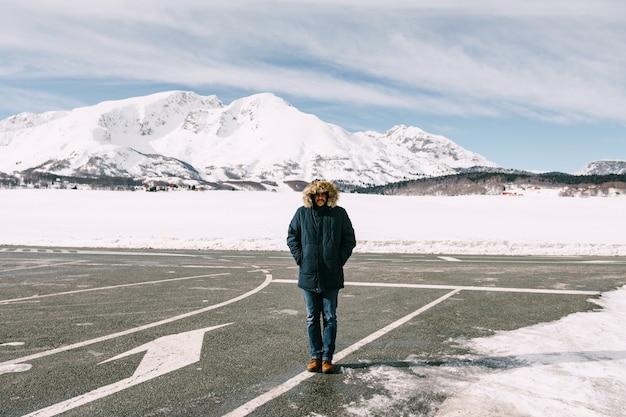 Um homem com uma jaqueta de inverno com capuz está de pé no asfalto coberto de neve, tendo como pano de fundo as montanhas brancas cobertas de neve de montenegro. foto de alta qualidade