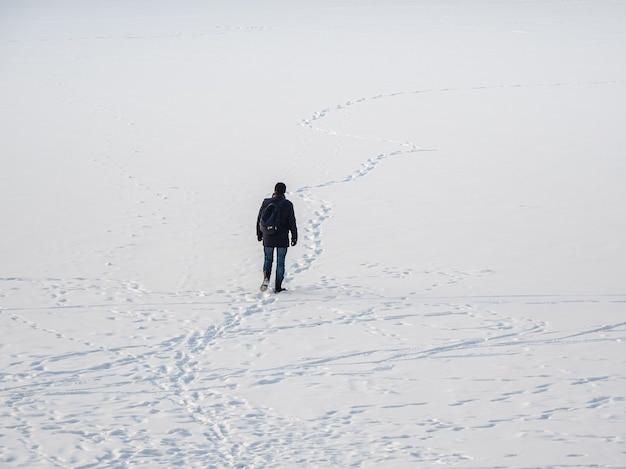 Um homem com uma jaqueta preta com uma mochila andando na neve, pegadas na neve, atrás.