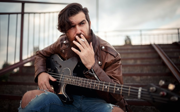 Um homem com uma longa barba em uma jaqueta de couro marrom e jeans rasgados fuma um cigarro e segura uma guitarra elétrica enquanto está sentado nos degraus