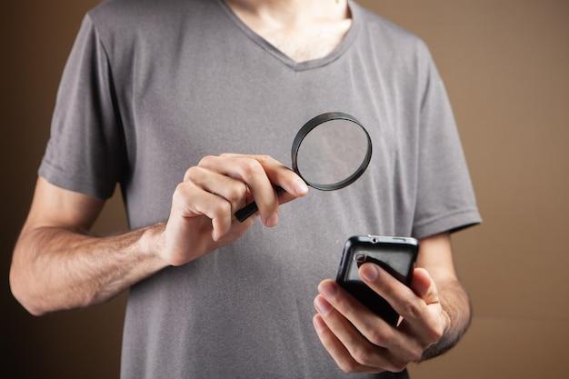 Um homem com uma lupa olha para o telefone em um fundo marrom