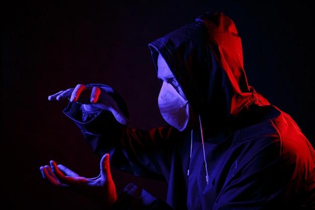Um homem com uma máscara e uma roupa de proteção química em luz vermelha e azul. lute contra o vírus. covid-19