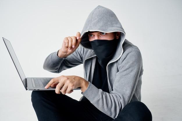 Um homem com uma máscara está sentado no chão em frente a um crime de invasão de computador laptop