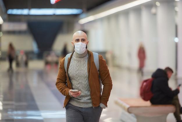 Um homem com uma máscara facial de médico está segurando um smartphone e caminhando enquanto espera por um trem no centro da estação de metrô
