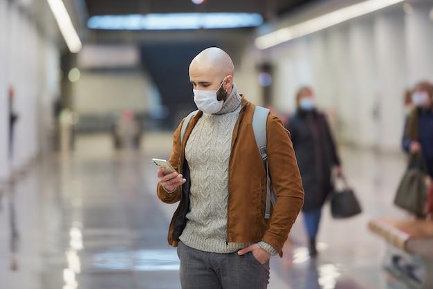 Um homem com uma máscara facial de médico está usando um smartphone enquanto espera o trem no centro da estação de metrô