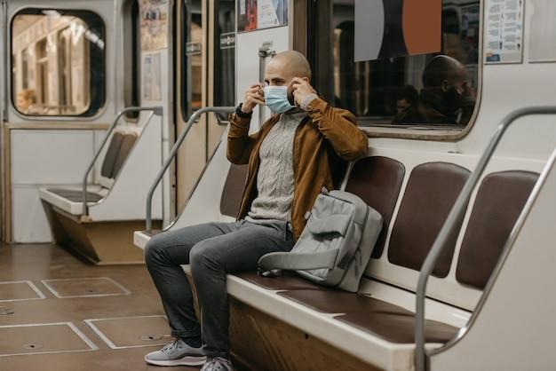 Um homem com uma máscara facial de médico na estação de metrô