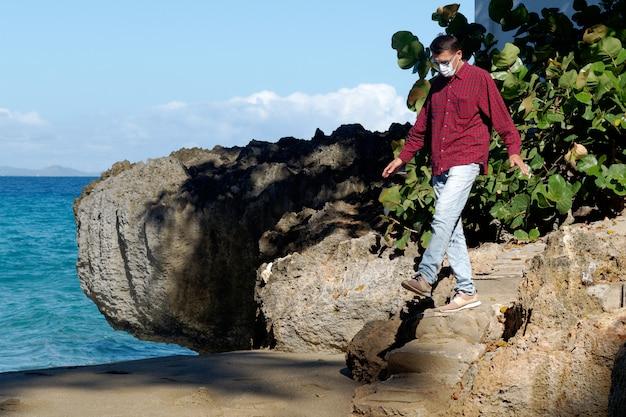 Um homem com uma máscara médica caminha perto do oceano.