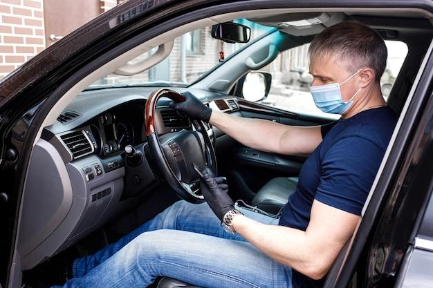 Um homem com uma máscara médica descartável e luvas em um carro com um telefone na mão