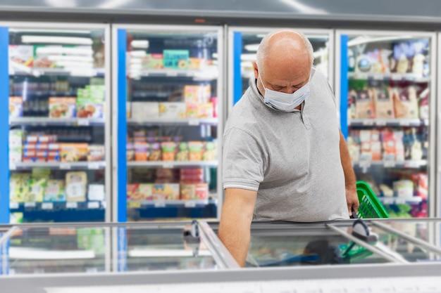Um homem com uma máscara médica na seção de alimentos congelados de um supermercado. pandemia do coronavírus.