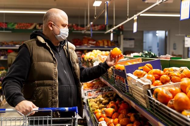 Um homem com uma máscara médica na seção de vegetais de um supermercado
