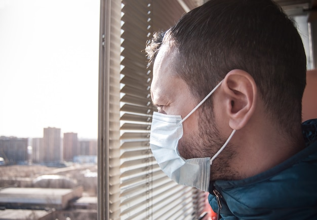 Um homem com uma máscara médica olha da varanda. está em quarentena.