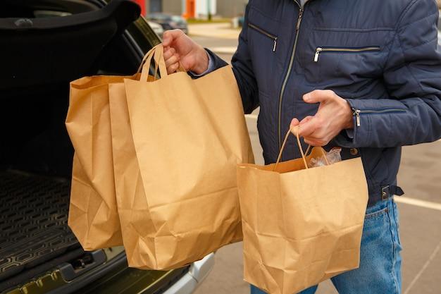 Um homem com uma máscara protetora no rosto coloca pacotes de comida no carro