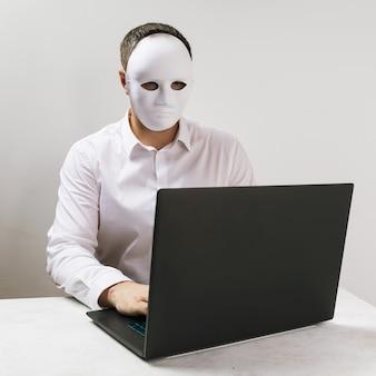 Um homem com uma máscara trabalha atrás de um laptop o conceito de anonimato na internet