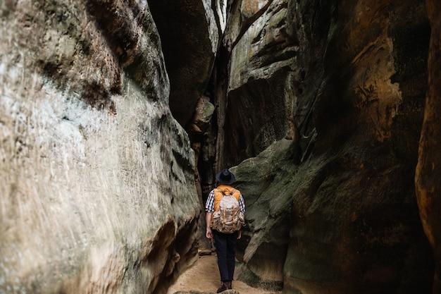 Um homem com uma mochila desce um desfiladeiro na montanha