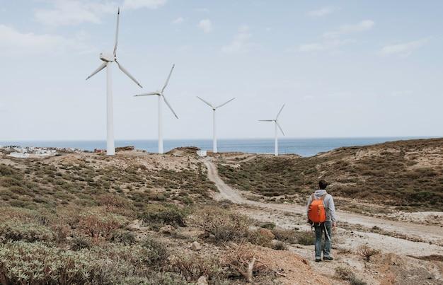 Um homem com uma mochila vermelha em pé olhando para os moinhos de vento