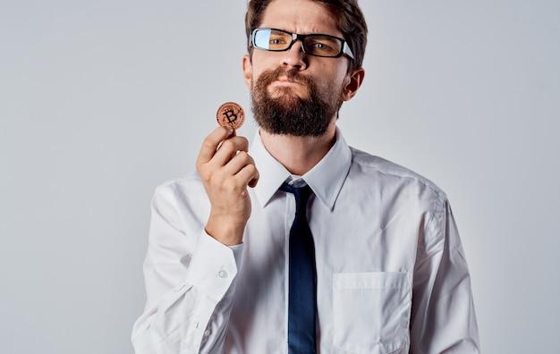 Um homem com uma moeda de ouro nas mãos em um fundo claro olhar intrigado da criptomoeda bitcoin