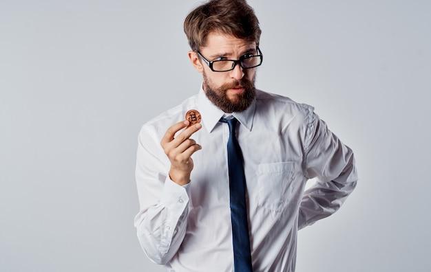 Um homem com uma moeda de ouro nas mãos sobre um fundo claro parece intrigado com a criptomoeda bitcoin