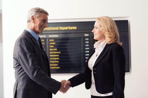 Um homem com uma mulher aperta as mãos perto do horário