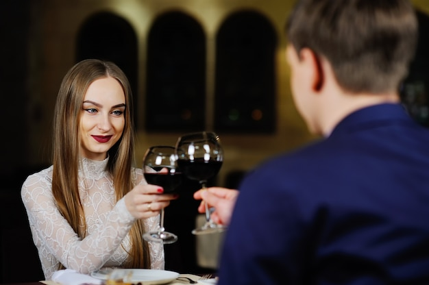 Um homem com uma mulher bebendo vinho tinto em um restaurante