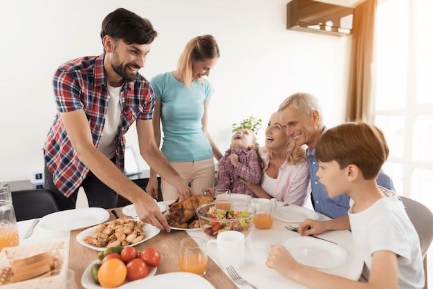 Um homem com uma mulher serve um jantar festivo na mesa