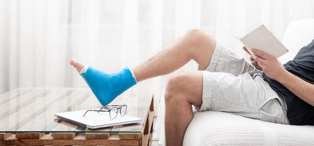 Um homem com uma perna quebrada engessada lê livros contra uma parede clara do interior da sala.