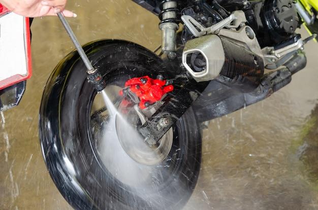 Um homem com uma pistola de água de alta pressão lavando uma motocicleta