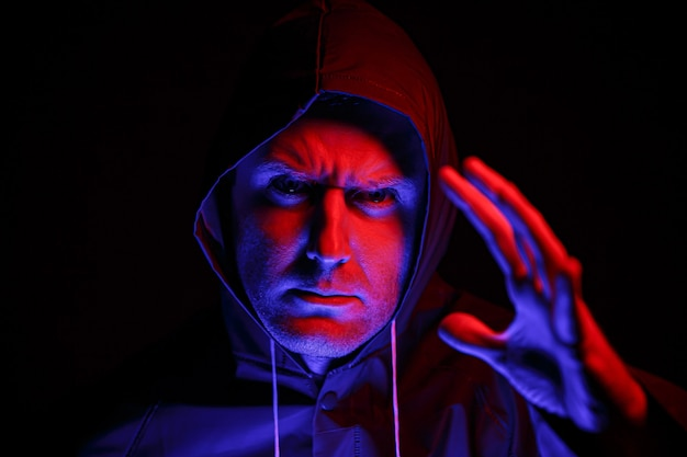 Um homem com uma roupa de proteção em um quarto escuro. conceito de imagem de halloween. proteção contra vírus. iluminado com luzes coloridas